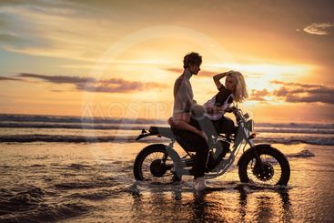 side view of passionate couple cuddling on motorbike at...