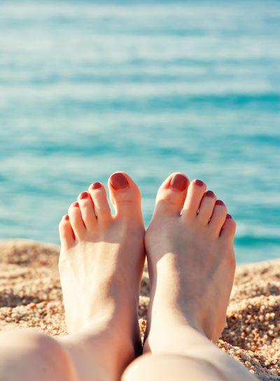 Close up female feet at sandy beach