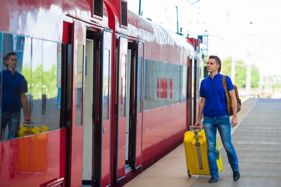 Young caucasian man with luggage at station traveling by...
