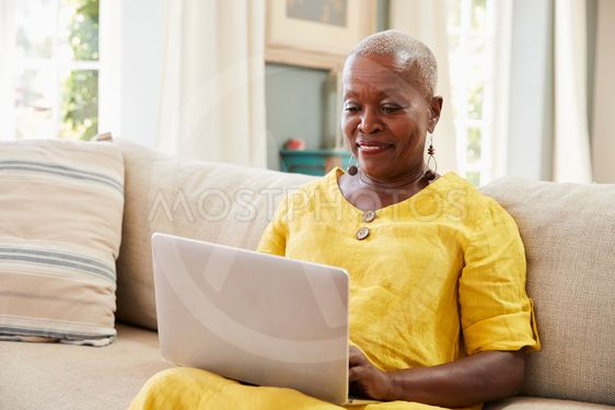 Senior Woman Sitting On Sofa Using Laptop At Home Together