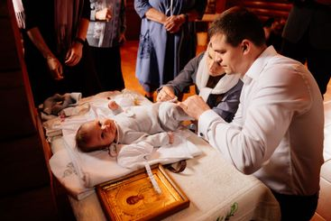 parents dress their child on a table in the Church. the...