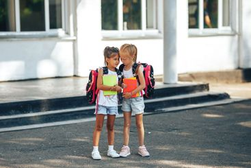 Two schoolgirls are talking near the school, back to...