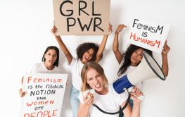 Displeased young women holding blank with girl power