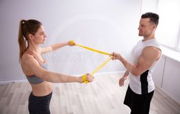 Young Woman With Gym Trainer Doing Exercise