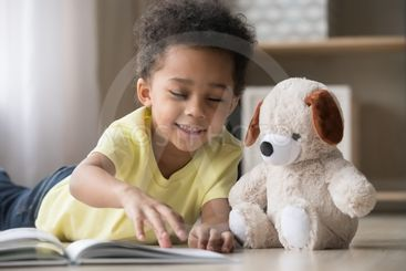 Happy african little boy playing alone reading book to toy