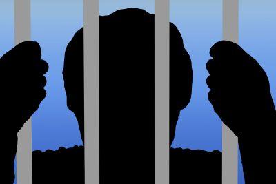 man behind bars in prison