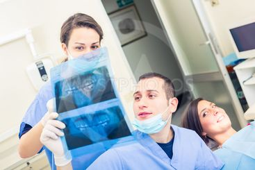 Dentist and dental assistant examining an X-ray