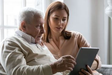 Caring grownup daughter teaching elderly father to use...