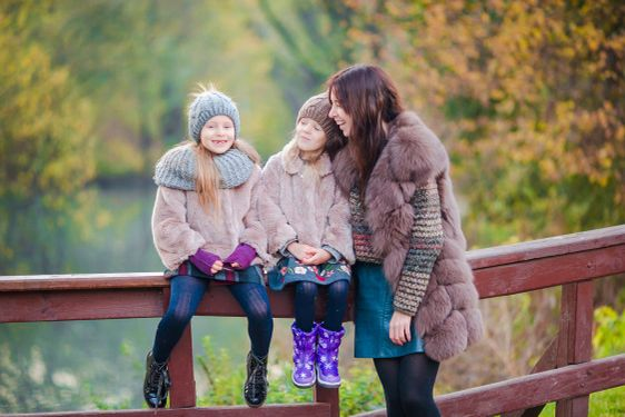 Adorable little girls with mother in autumn park...
