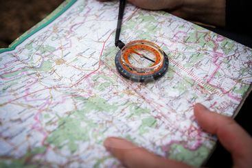 man holding compass and map