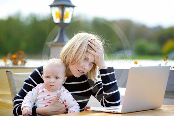 Tired young mother working oh her laptop