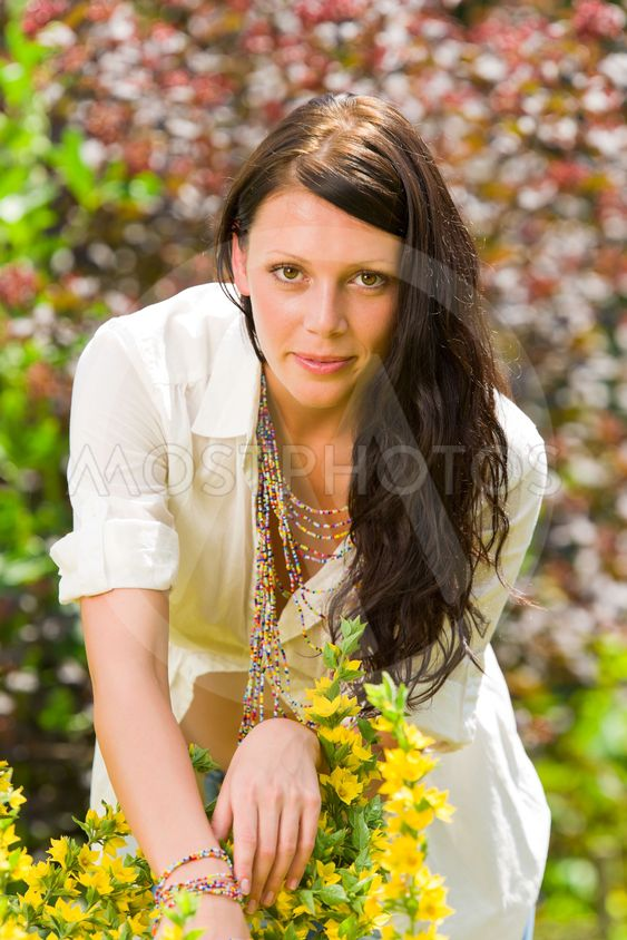 Beautiful woman sunny garden care yellow flowers