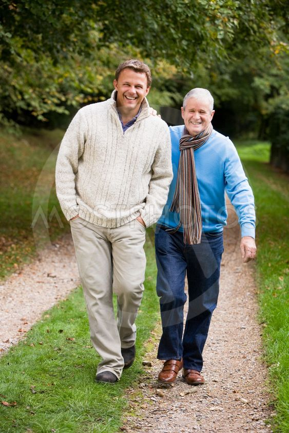 Adult father and son walking along path