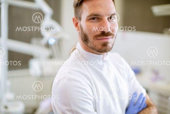 Handsome dentist posing in modern dental office
