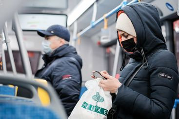 A young woman in a protective medical mask on the bus...