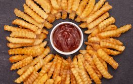 Fries arranged in a circle around ketchup bowl