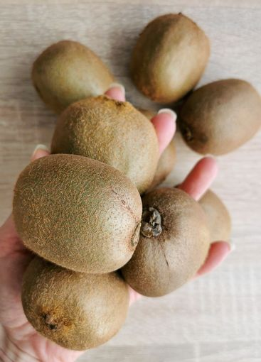 Group of ripe whole green kiwi in hand