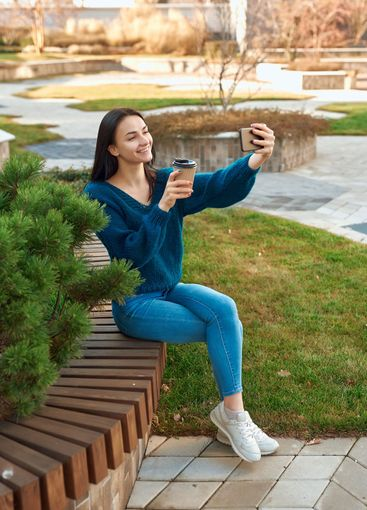 Charming lady posing for selfie on a bench in beautiful...