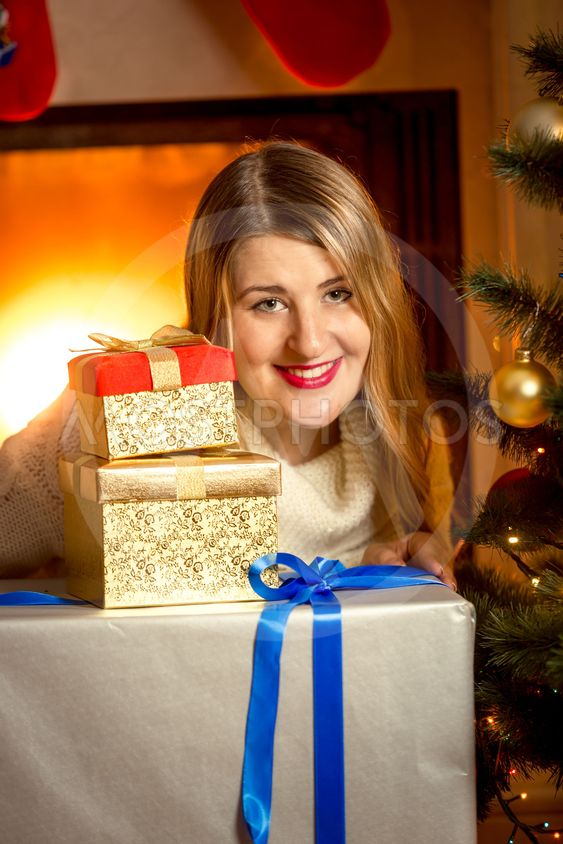 beautiful smiling woman posing with Christmas presents at...