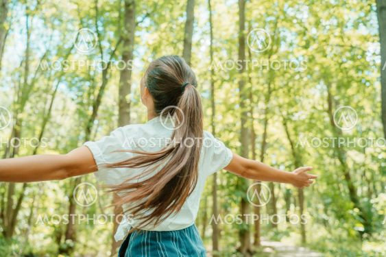 Happy woman in forest with open arms from behind...