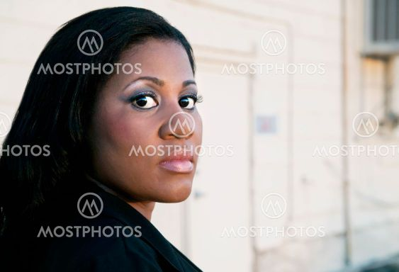 African American Business Woman by Industrial Building