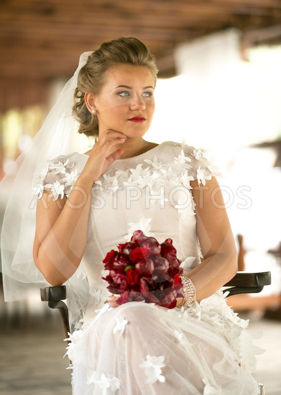 portrait of beautiful elegant bride with red bouquet...