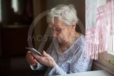 Elderly woman with a smartphone in home.
