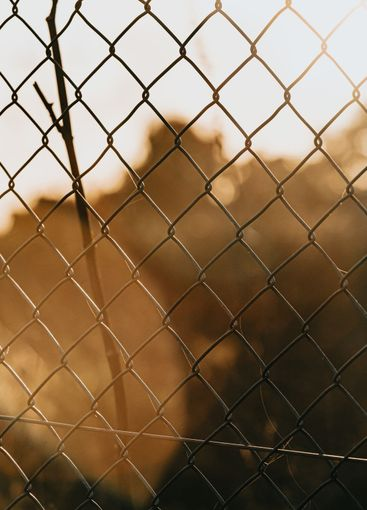 Fence during a colorful sunset background, orange and...