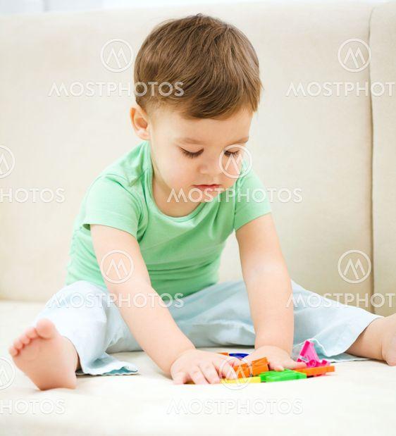 Little boy spelar med leksaker