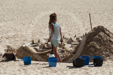 woman building an artistic sand castle on the beach