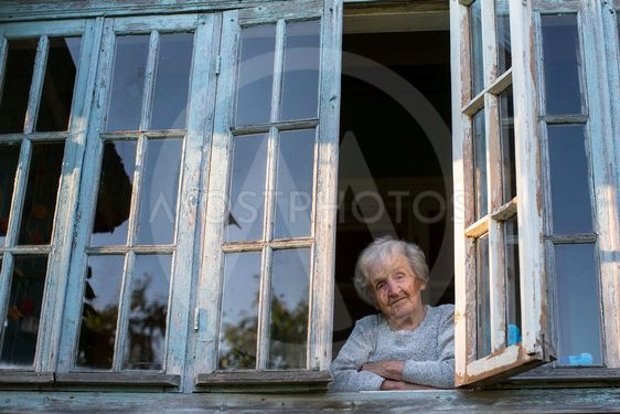 Grandmother, an elderly woman looks from the window of...