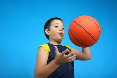 Boy playing basketball. blue background
