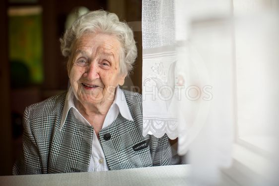 Positive elderly woman sitting in the room.