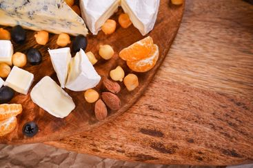 pieces of cheese on a wooden Board. empty space.