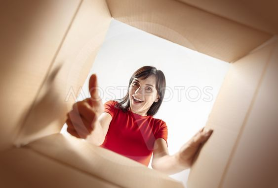 Woman unpacking and opening carton box and looking inside