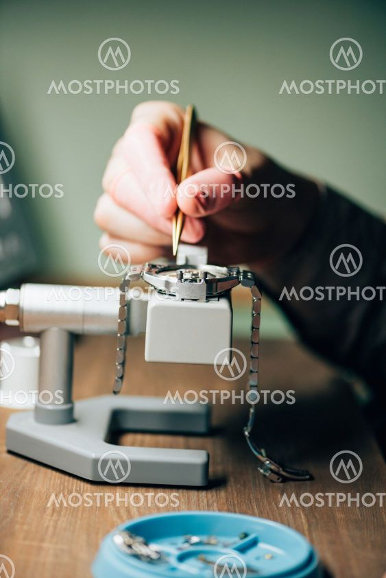 Cropped view of watchmaker repairing wristwatch by tool...