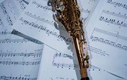 A saxophone lying on sheet music