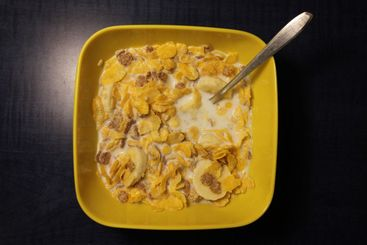 Breakfast cereal from above in a yellow plastic bowl
