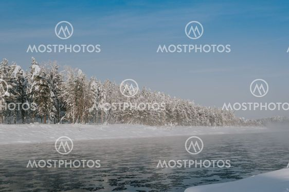 Frosty fog over winter river with snow and forest on...
