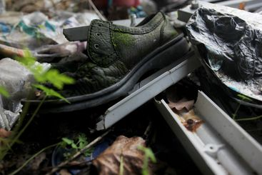 Old left shoe between other trash
