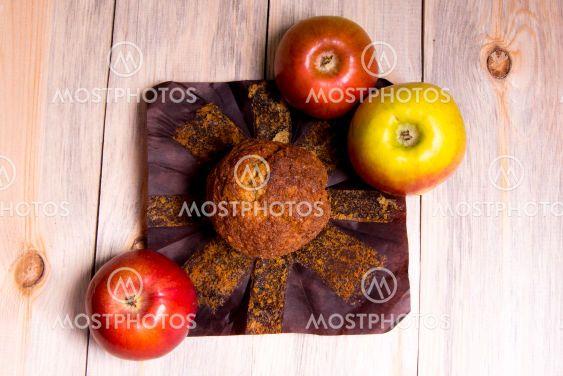 Кекс,пирожное с красно жёлтыми яблоками на деревянном...