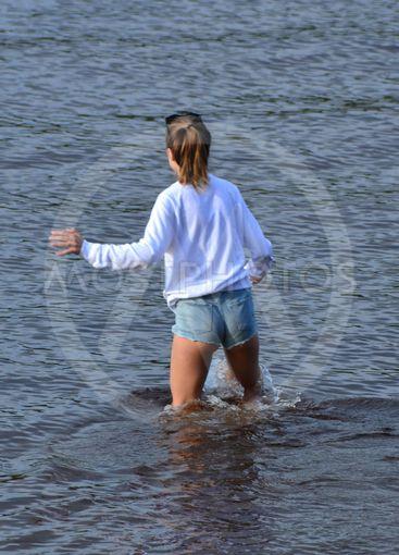 Flicka badar med kläder på