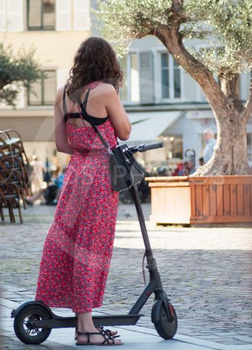 young woman standing with electric scooter...