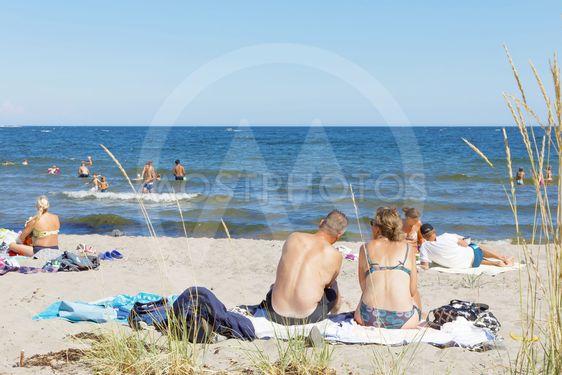 Sunbathing people relaxing on the sand beach, blue sky in...