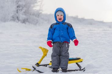 little boy stands near the snow scooter and shouts
