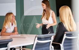 Group Of Businesswomen Sitting Around Boardroom Table And...