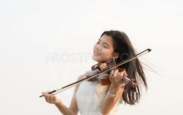 Happy woman playing violin on the beach.