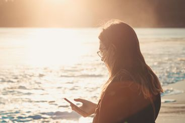 Young woman checking his cellphone in the beach during a...