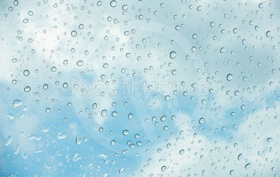 Drops of water on glass window over blue sky .