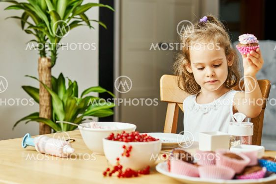 girl in a white dress decorates and eats a delicious...